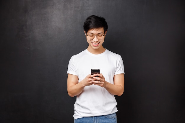 Technologie, gadgets en mensen concept. glimlachend tiener aziatische man spelen op telefoon, sms'en vriend met behulp van telefoon messanger, gebruik nieuwe app om foto's sociale media, zwarte muur te bewerken