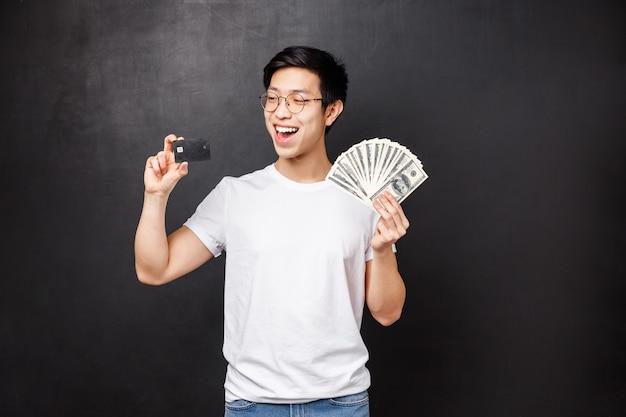 Technologie, geld en prijzen concept. portret van opschepperige glimlachende, gelukkige aziatische kerel wordt rijk, gelukkig om prijs te winnen, dollars en creditcard te houden, beslissend hoe geld te investeren,