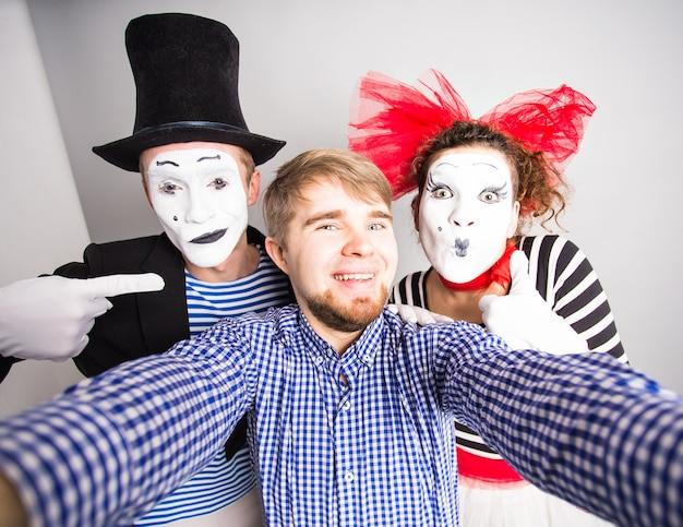 Technologie internet en geluk concept. jonge mannen en mime die zelffoto selfie met smartphone camera grijze achtergrond nemen.