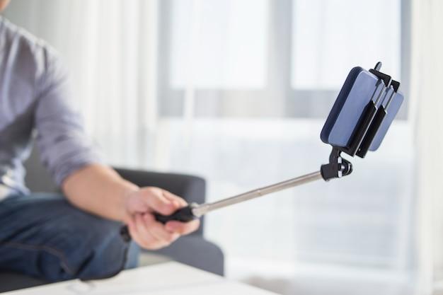 Technologie internet en geluk concept. jonge vrouw grappige meid nemen zelfbeeld selfie met smartphone camera op stok terwijl zitten op de bank thuis
