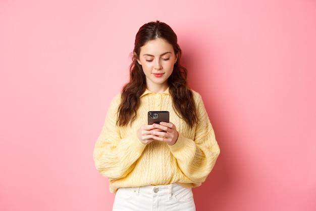 Technologie. jonge lachende vrouw chatten op sociale media, bericht lezen op smartphone, staande tegen roze muur.