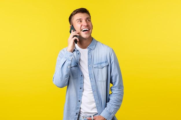 Technologie, levensstijlconcept. vrolijke knappe glimlachende man die een gelukkig gesprek aan de telefoon heeft, een vriend belt, er enthousiast uitziet en een smartphone in de buurt van het oor houdt, gele achtergrond.