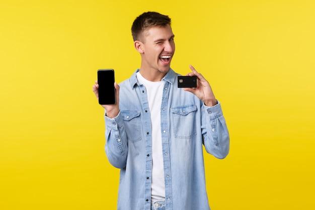 Technologie, lifestyle en reclame concept. brutale knappe man die online bestelling plaatst, op internet winkelt met mobiele app, smartphonescherm en creditcard toont, gele achtergrond