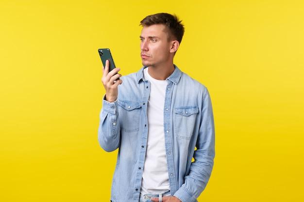 Technologie, lifestyle en reclame concept. geërgerde en gefrustreerde jonge man verbaasd over plotseling beëindigd gesprek, kijkend naar geïrriteerde mobiele telefoon, staande over gele achtergrond.