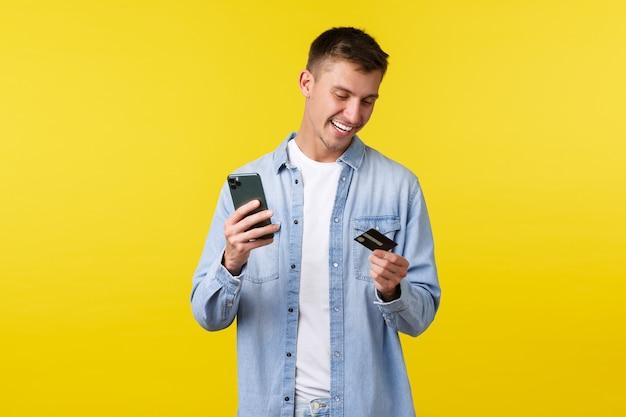 Technologie, lifestyle en reclame concept. knappe gelukkige man die online bestelling plaatst, vliegtickets boekt met smartphone-app, creditcard bekijkt en mobiele telefoon vasthoudt, gele achtergrond.