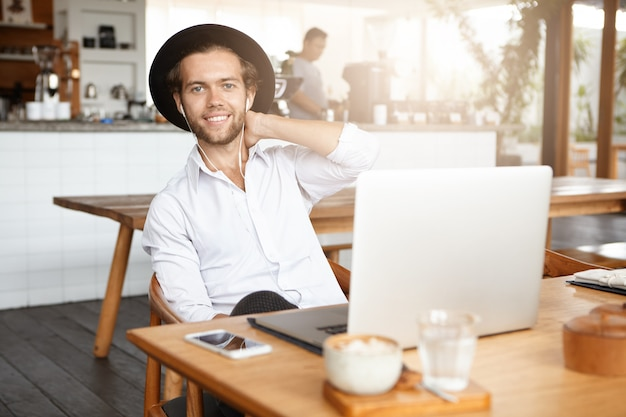 Technologie maakt het leven gemakkelijker. modieuze bebaarde man in oortelefoons met behulp van gratis draadloze internetverbinding op zijn laptop, luisteren naar muziek of audioboek online tijdens de lunch in modern café-interieur