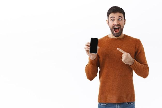 Technologie, mensen en communicatieconcept. portret van een enthousiaste, gelukkig lachende blanke man die met de vinger naar het scherm van de mobiele telefoon wijst, bonussen krijgt in de online smartphone-app, er onder de indruk uitziet