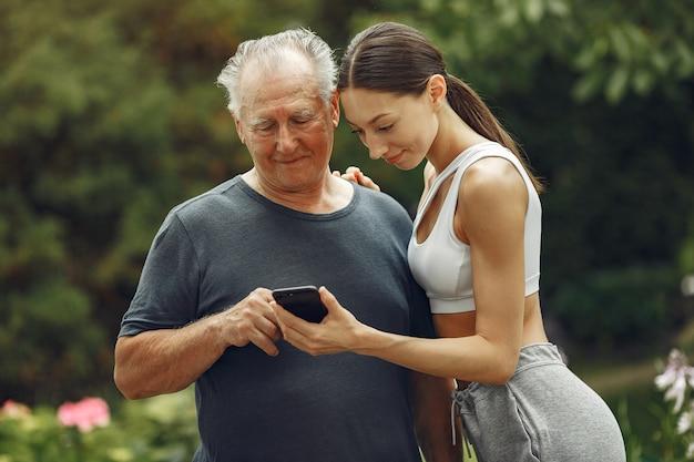 Technologie, mensen en communicatieconcept. senior man in zomer park. grangfather met kleindochter.
