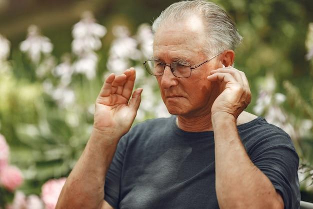 Technologie, mensen en communicatieconcept. senior man in zomer park. grangfather via een telefoon.