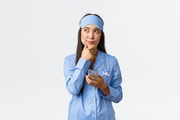 Technologie, mensen en thuis vrije tijd concept. doordachte en creatieve schattige vrouwelijke blogger, aziatisch meisje in pyjama en slaapmasker heeft een idee, denkt en houdt een mobiele telefoon vast, maakt post.
