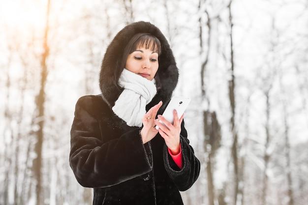 Technologie, mensen en winter concept - jonge vrouw met smartphone en winterlandschap sneeuwvlokken