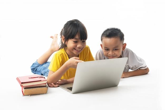 Technologie met leren en onderwijs, groep aziatische kinderen die op laptop op witte achtergrond kijken