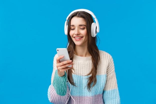 Technologie, millennials en lifestyle concept. zorgeloze schattige brunette vrouwelijke student zet een koptelefoon op, plug-in smartphone kiest lied en glimlacht, staande blauwe achtergrond maakt afspeellijst voor studie.