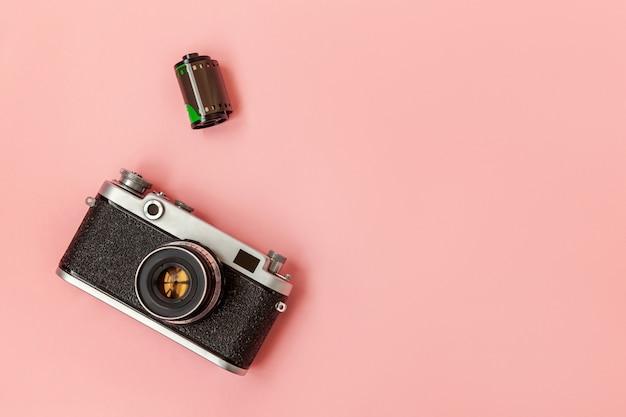 Technologie ontwikkeling hipster fotograaf hobby klassiek geheugen reis concept. vintage film fotocameralens en filmrol op roze pastel trendy moderne mode pin-up achtergrond