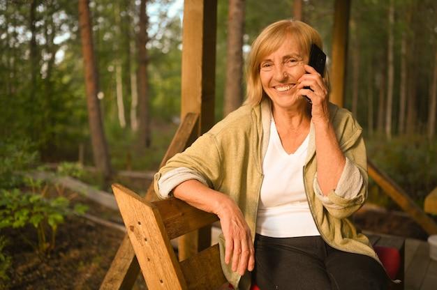 Technologie ouderdom mensen concept ouderen senior oude gelukkig lachende vrouw spreekt mobiele smartphone
