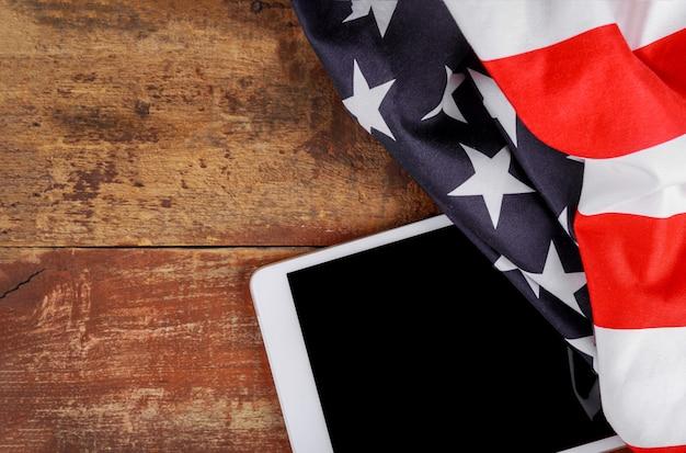 Technologie, patriottisme, verjaardag, nationale feestdagen van tablet op amerikaanse vlag en onafhankelijkheidsdag