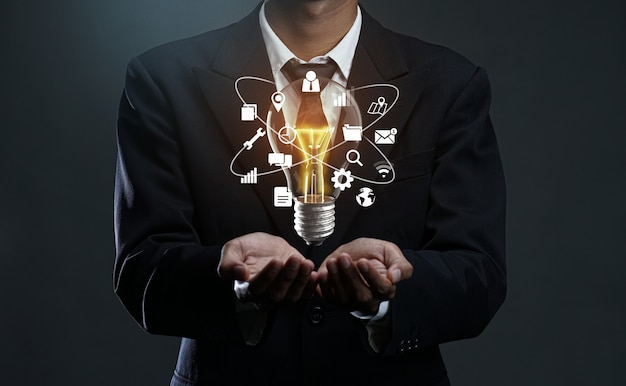 Technologie pictogrammen gloeiende lamp drijvend op zakenmanhand.