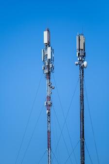 Technologie van telecommunicatie gsm 5g, 4g, 3g toren. mobiele telefoonantennes op het dak van een gebouw. ontvangst- en zendstations met blauwe luchten op de achtergrond.