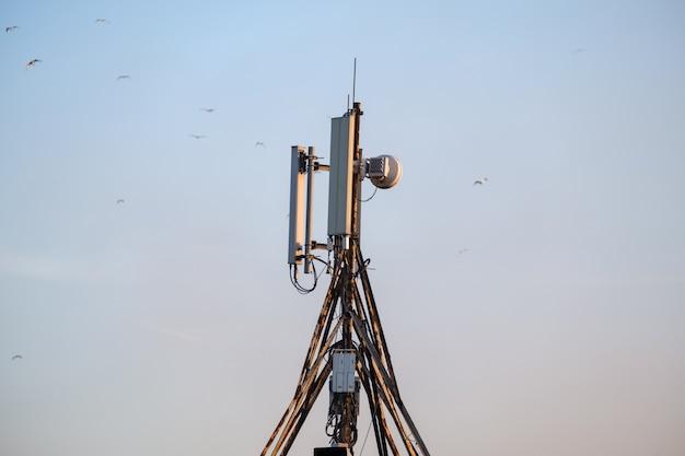Technologie van telecommunicatie gsm 5g, 4g, 3g toren. mobiele telefoonantennes op het dak van een gebouw. ontvangst en zendstations met vogels op de achtergrond.