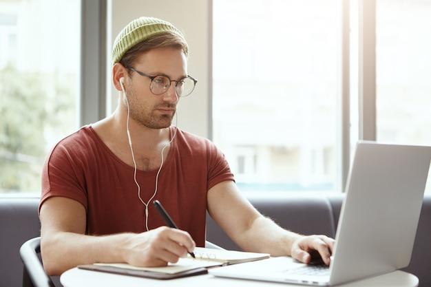 Technologie, werk en baanconcept. succesvolle mannelijke vertaler werkt op afstand, schrijft in notitieblok met pen