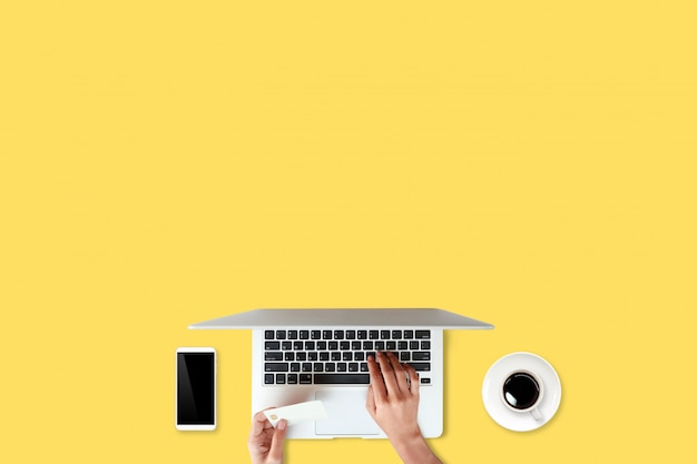 Technologie werktafel met vrouw handen op laptopcomputer, creditcard, koffiekopje en mobiele telefoon op geel (of winkelen en betaling online concept)