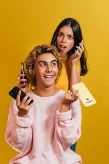 Technologieconcept. verticale opname van twee blanke modellen die poseren met smartphones voor een gele muur. jonge brunette vrouw gekleed in geel en jonge blonde man gekleed in roze trui