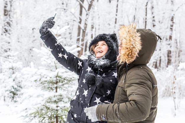 Technologieën en relatie concept - gelukkig lachend paar dat een selfie in een winter forest