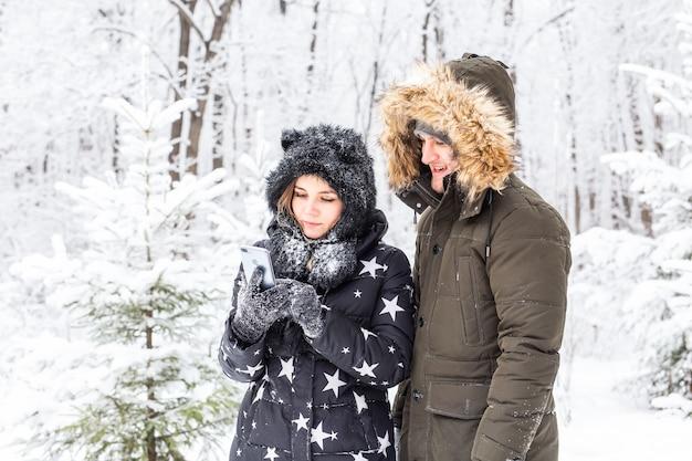 Technologieën en relatieconcept - gelukkig lachend paar dat een selfie in een de winterbos buiten neemt.