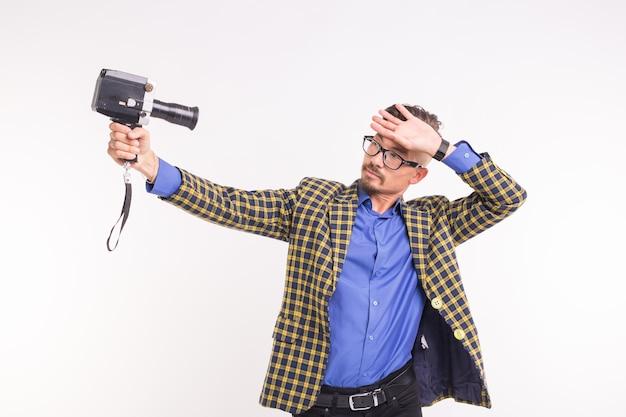 Technologieën, fotograferen en mensen concept - knappe jonge man met retro camera glimlachend op witte achtergrond.