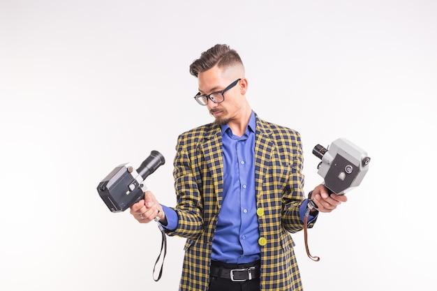 Technologieën, fotograferen en mensen concept - portret van grappige jonge brunette man selfie te nemen met twee camera's op witte achtergrond.