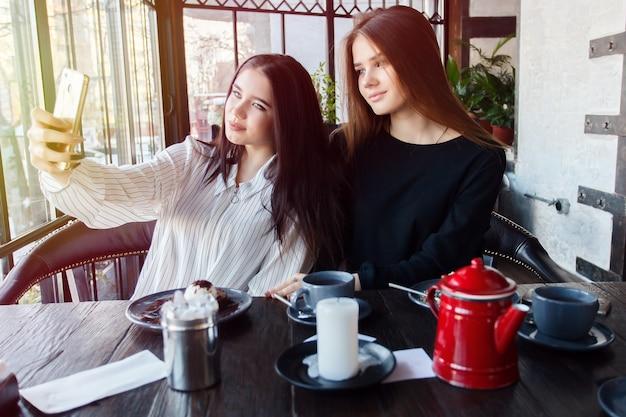 Technologieën, levensstijl, voedsel, mensen, tieners en koffieconcept - twee jonge vrouwen die selfie met smartphone nemen in het stadscentrum. geluksconcept over mensen en technologie