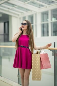 Technologieën maken winkelen gemakkelijker. mooie jonge vrouw met boodschappentassen met behulp van haar slimme telefoon met glimlach terwijl je op de kledingwinkel