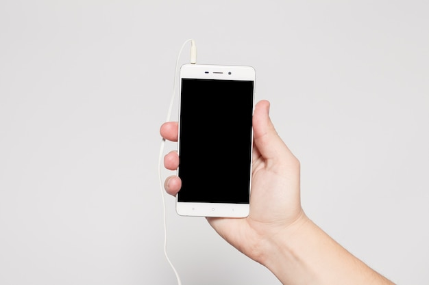 Technologieën, mensen en lifestyle concept - hand houden telefoon zwart scherm, mockup nieuwe smartphone moderne stijl mat witte kleur