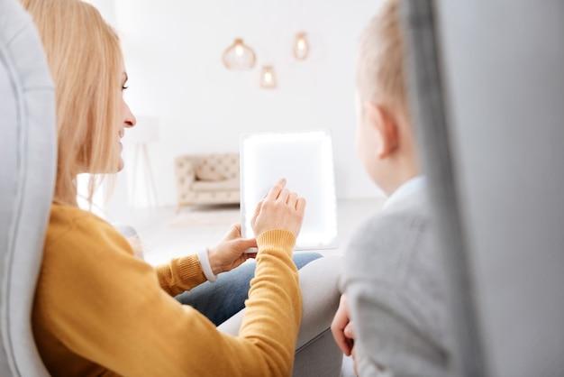 Technologisch apparaat. close-up van een moderne nieuwe tablet die in de hand is van een aardige positieve vrouw terwijl ze het aan haar zoon laat zien