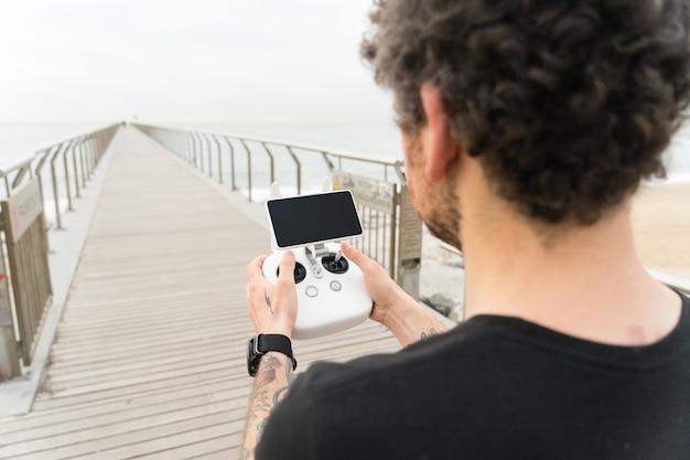 Technologisch onderlegde hipster of jonge generatie millennial professionele fotograaf gebruikt afstandsbediening om drone- of quadrocopter-gadget in de lucht te besturen