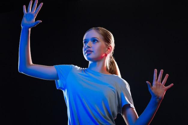 Technologisch proces. slimme jonge vrouw die voor het transparante scherm staat terwijl ze haar handen erop drukt