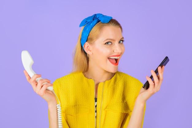 Technologische evolutie stijlvolle vrouw houdt bekabelde telefoon mobiele telefoon glimlachende vrouw in hoofdband houdt vast