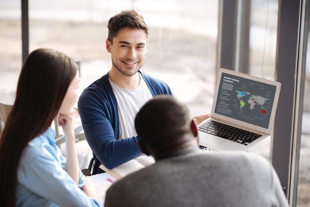 Technologische ontwikkeling. knappe jonge kerel die moderne laptop houdt en presentatie geeft aan zijn internationale collega's.