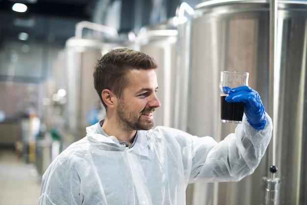 Technoloog die de productkwaliteit controleert in de productie-installatie voor drankalcohol