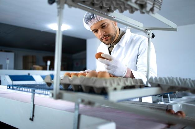 Technoloog in steriele kleding, haarnetjes en hygiënische handschoenen die de productie van industriële eieren in de voedselfabriek controleren.