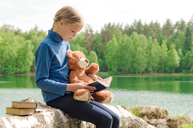 Teddy bear en schattig meisje gelezen boek over picknick in de zomer de natuur.