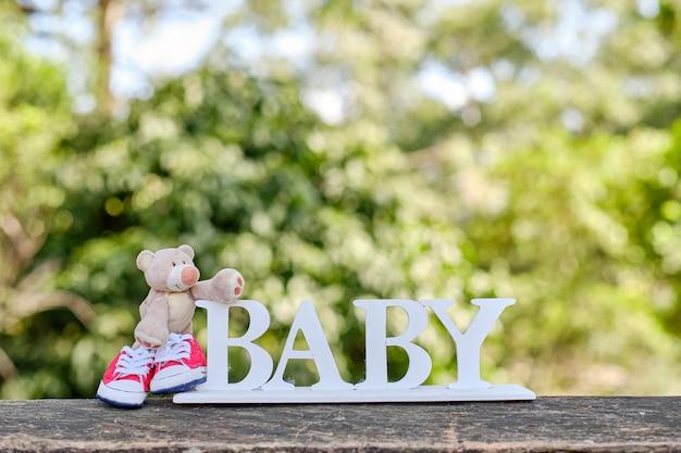 Teddy met rode gympen en bordje met baby erop