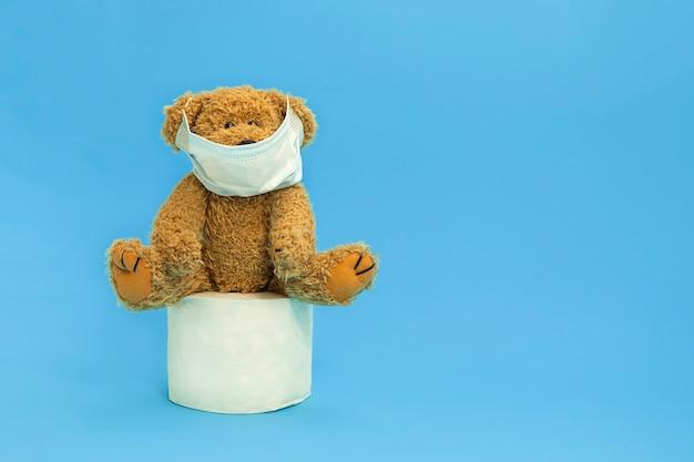 Teddybeer die gezichtsmasker draagt en op een toiletpapierbroodje zit op blauwe achtergrond
