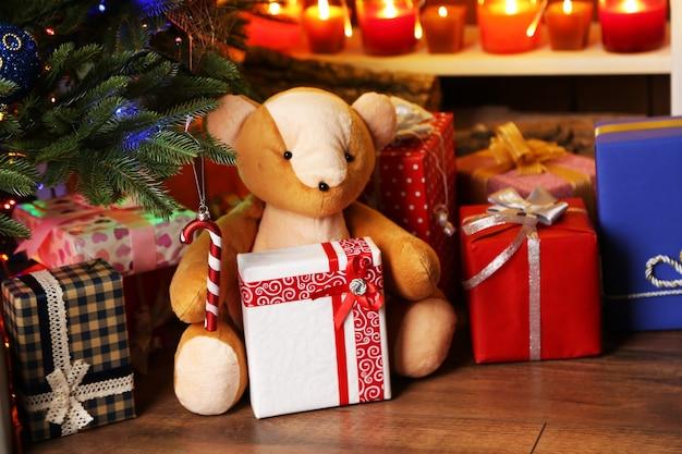 Teddybeer en geschenkdozen in de buurt van kerstboom, close-up