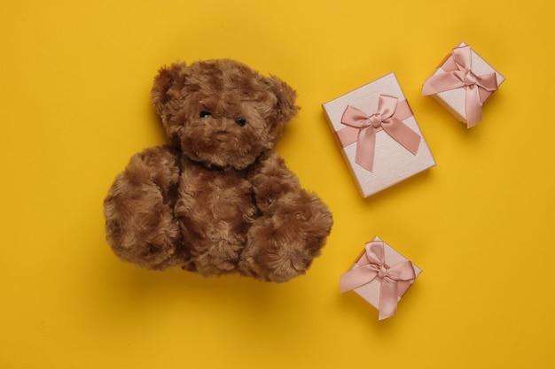 Teddybeer en geschenkdozen op gele achtergrond. kerstmis, verjaardag concept. bovenaanzicht