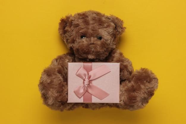 Teddybeer en giftdoos op gele achtergrond. kerstmis, verjaardag concept. bovenaanzicht
