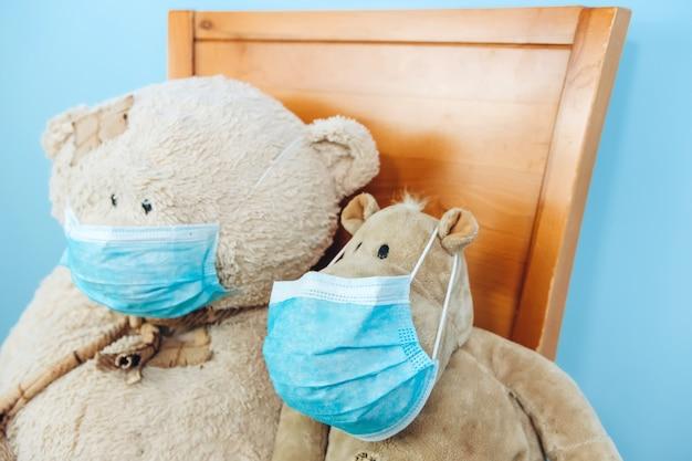 Teddybeer en nijlpaard in een medisch masker op een blauwe muur. concept van 2019-20 coronavirus covid-19 pandemie.
