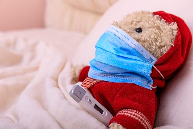 Teddybeer in een medisch masker in het bed. ademhalingsmedicijnen. kinderen en ziekte covid-2019 ziekteconcept.