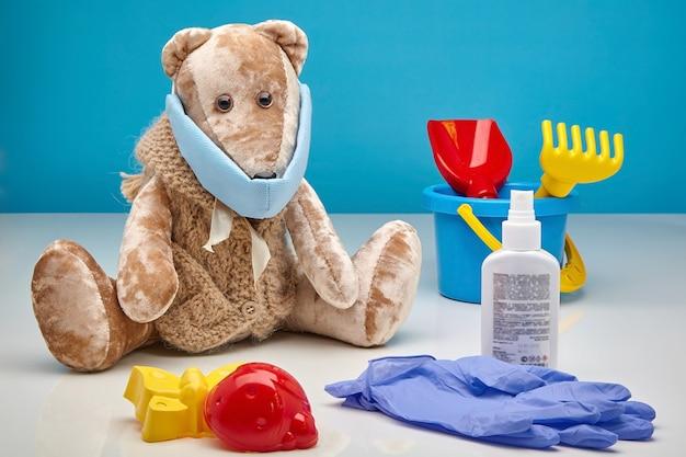 Teddybeer in een medisch masker, latex handschoenen, een antiseptisch middel en verspreid kinderspeelgoed op een blauwe muur. het concept om kinderen te beschermen tegen virale infecties, de tweede golf van coronavirus