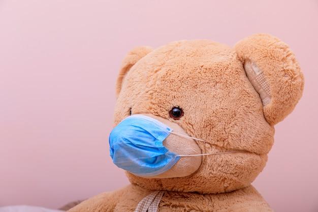 Teddybeer in een medisch masker op een witte achtergrond. ademhalingsmedicijnen. coronavirus of covid 19-concept.
